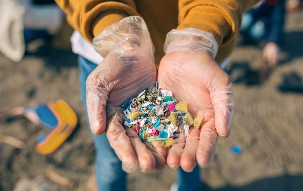 Man holding a handful of microplastics